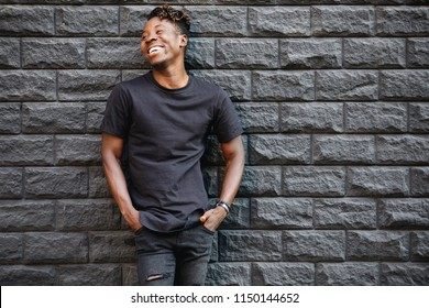 Handsome african american man in black t-shirt laughing against brick wall