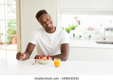 Handsome african american man eating heatlhy cereals and berries as breakfast
