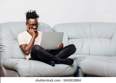 handsome African American man in glasses sitting with laptop on sofa