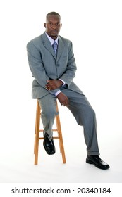 Handsome African American man in a gray business suit sitting on a stool.