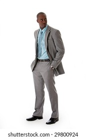 Handsome African American man in gray suit with smile standing with hands in pocket, isolated