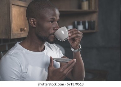 Handsome african american man having his morning coffee at home