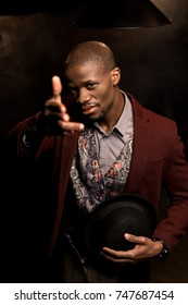 handsome african american man holding hat and pointing at you with hand gun