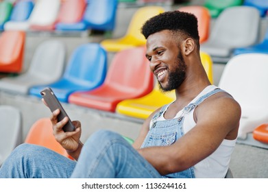 Handsome african american man at jeans overalls witjh mobile phone at hands posed on colored chairs at stadium. Fashionable black man portrait.