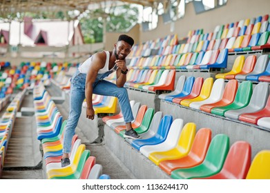 Handsome african american man at jeans overalls posed on colored chairs at stadium. Fashionable black man portrait.