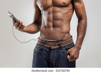 Handsome African American man listening music on his mobile device after sport exercise
