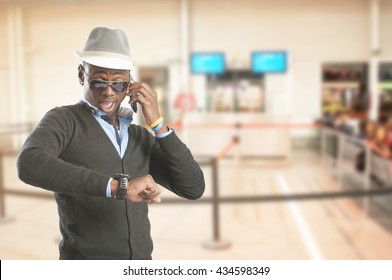 Handsome african american man  looking at his watch at airport