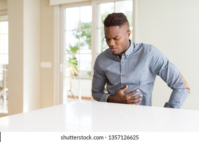 Handsome african american man on white table with hand on stomach because indigestion, painful illness feeling unwell. Ache concept.