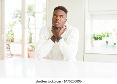 Handsome african american man on white table shouting and suffocate because painful strangle. Health problem. Asphyxiate and suicide concept.