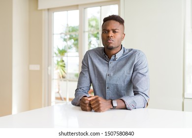 Handsome african american man on white table skeptic and nervous, frowning upset because of problem. Negative person.