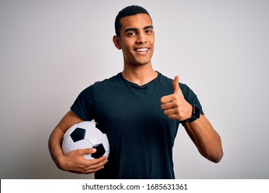 Handsome african american man playing footbal holding soccer ball over white background doing happy thumbs up gesture with hand. Approving expression looking at the camera showing success.