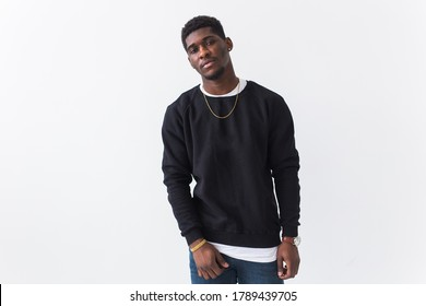 Handsome African American man posing in black sweatshirt on a white background with copyspace. Youth street fashion photo with afro hairstyle.