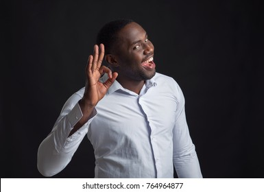 Handsome african american man shows a gesture that everything is OK, very good, excellent. Surprised black businessman.