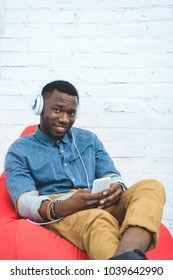 Handsome african american man with smartphone listening to music in earphones and sitting in bean bag