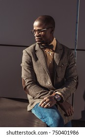 Handsome african american man in suit sitting on concrete structure and looking aside