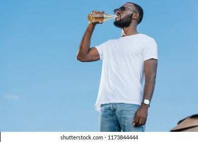 handsome african american man in sunglasses drinking soda against blue sky