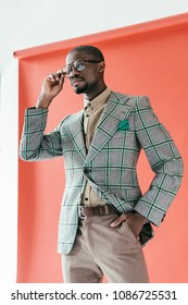 handsome african american man in trendy eyeglasses posing on red