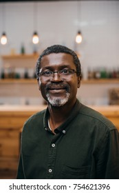 handsome african american mature man in front of blurred bar counter