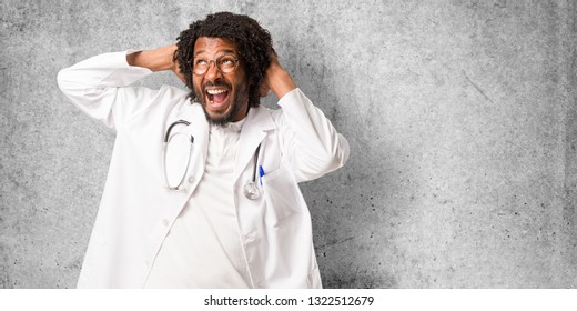 Handsome african american medical doctor crazy and desperate, screaming out of control, funny lunatic expressing freedom and wild