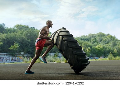 Handsome african american muscular man flipping big tire outdoor.