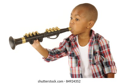 A handsome African American preschooler playing a black and gold clarinet.  Isolated on white.