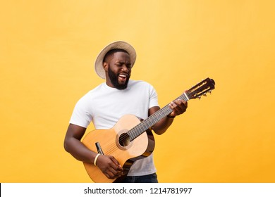 Handsome african american retro styled guitarist playing acoustic guitar isolated on yellow background.