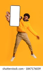 Handsome african american young man recommending new mobile application, collage. Excited black guy holding smartphone, showing blank screen, jumping up over orange studio background