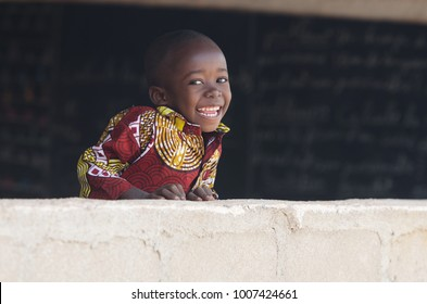 Handsome African Baby Boy Laughing Behind Wall at School