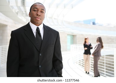 A handsome african business man with co-workers in background