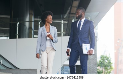 Handsome african businessman and attractive black businesswoman discussing work while walking outdoors