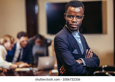 handsome african businessman looking on camera with group of businesspeople on background