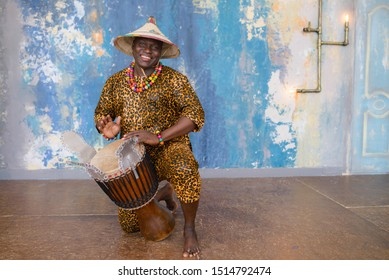 Handsome african drummer weared in traditional costume playing on djembe drum