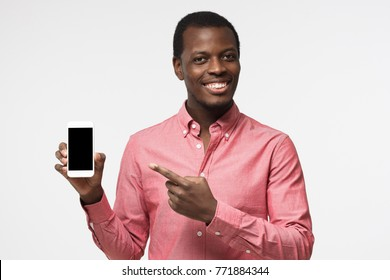 Handsome african guy in pink shirt isolated on grey background, presenting smart phone and pointing with finger at blank black screen with copyspace for ads