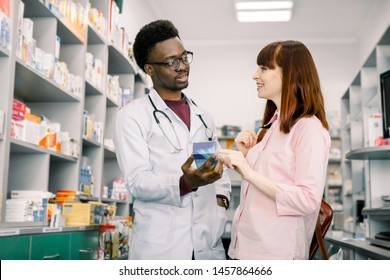 Handsome African male pharmacist talking with a beautiful female client in modern light pharmacy.