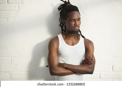 handsome african man with dreadlocks in a white vest on a white background