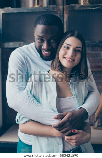 Handsome african man  embracing his beautiful  girl in kitchen