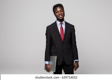 Handsome African man in formalwear move with laptop in hands while standing against grey background