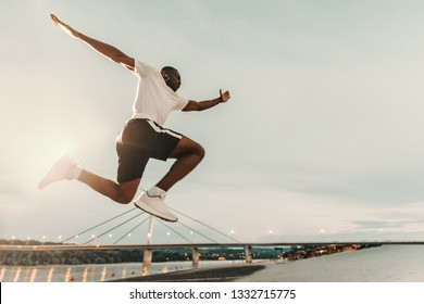 Handsome african man in sportswear running fast at the beach. Bottom view. in background bridge and river. It does not matter how slowly you go as ling as you do not stop.