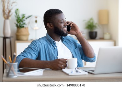 Handsome african man talking on the phone and drinking coffee while sitting at the office desk