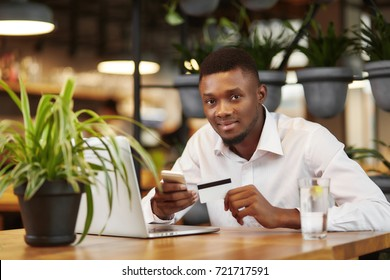 Handsome african man in white shirt smiling at camera, paying with plastic card in cafe, typing, sending money with smart phone and laptop. Student sending money from credit card. Internet shopping.