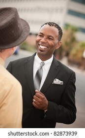 Handsome African-American businessman smiles while chatting with his friend