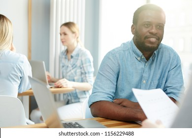 Handsome African-American man sitting at table and listening closely to colleague in brightly lit office