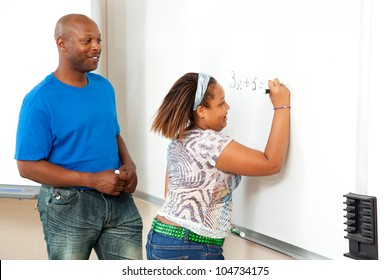 Handsome african-american math teacher works with a student at the board.