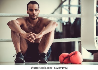 Handsome Afro American boxer with bare torso is looking at camera while sitting on the boxing ring