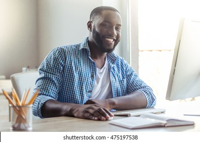 Handsome Afro American businessman in casual clothes is using a computer, looking at camera and smiling while working at home