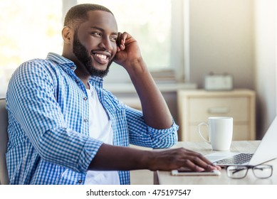 Handsome Afro American businessman in casual clothes is leaning on table, looking away and smiling while working at home