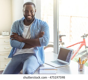 Handsome Afro American businessman in casual clothes is looking at camera and smiling while sitting with crossed arms on his working place at home