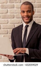Handsome Afro American businessman in classic suit is using a laptop, looking at camera and smiling, against white brick wall