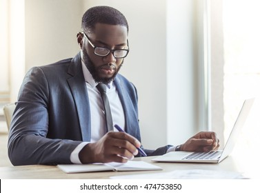 Handsome Afro American businessman in classic suit and eyeglasses is using a laptop and making notes while working in office