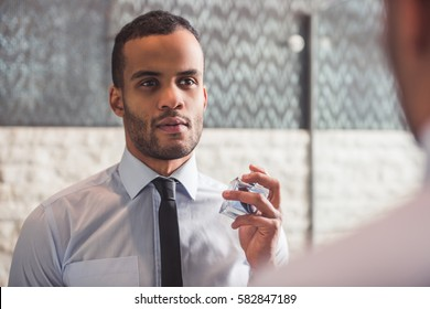 Handsome Afro American businessman in classic shirt and tie is using perfume while looking into the mirror in bathroom